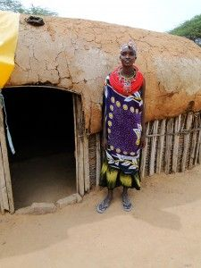 Judy, spokesperson for the women, outside a typical mud and dung house