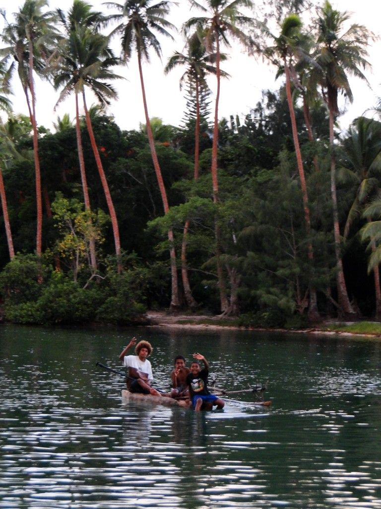 Local children sailing a pirogue on the second lagoon, Port Vila