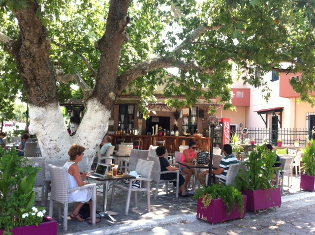 Under the leafy oak tree at Oasis Cafe in Agia Paraskevi