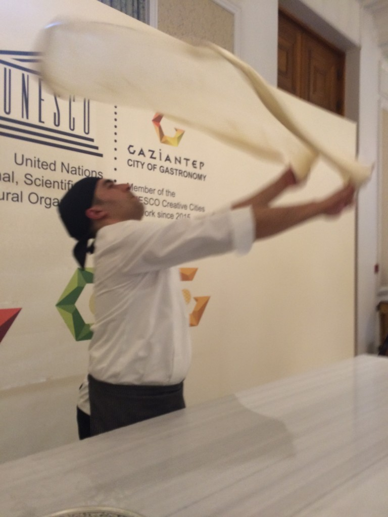 The baklava master swirling the pastry in the air