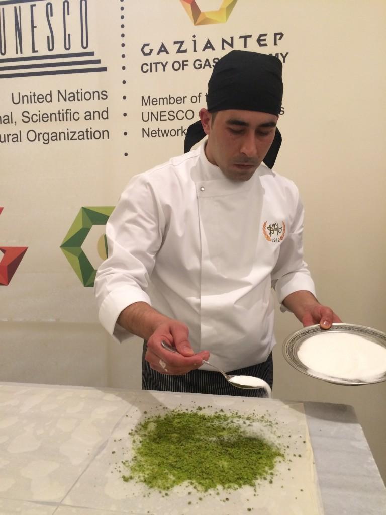 Making karma: a baklava master sprinkling sugar over ground fresh green pistachios
